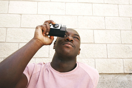 Young man taking shots with an analog camera