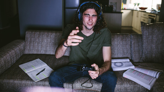 Student playing video game sitting at home