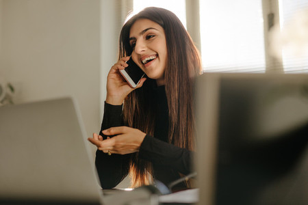 Businesswoman in casuals making a phone call in office