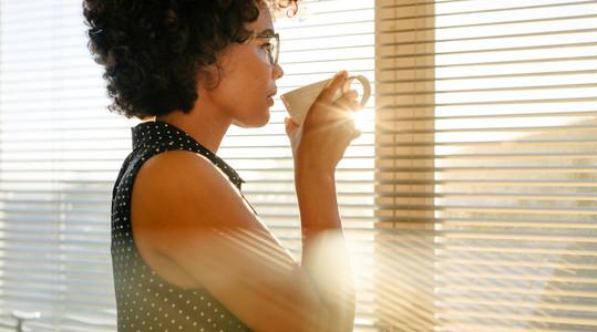 Businesswoman having coffee by office window