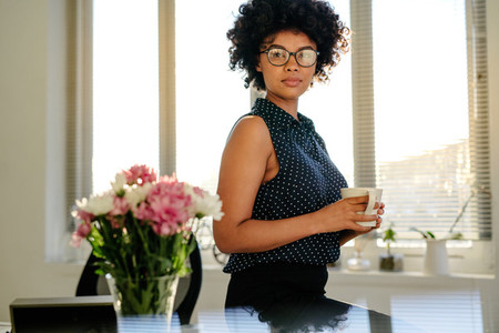 Confident woman in office with coffee