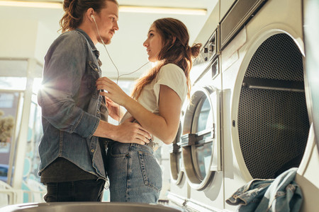 Couple in love standing together listening to music in laundry r