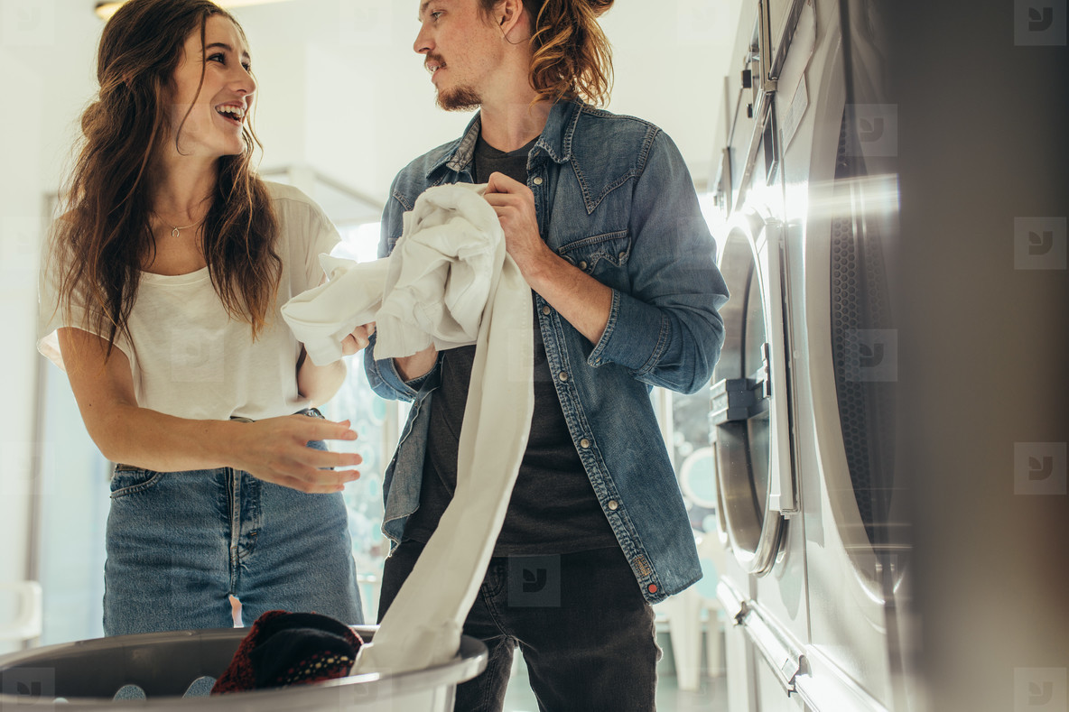 Smiling couple putting clothes in a washing machine together