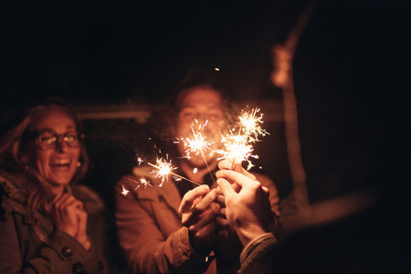 Friends lighting fire sparkles at night