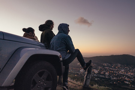 Friends sitting on a hilltop looking at the city below