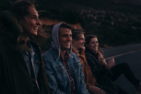 Group of friends sitting on a highway