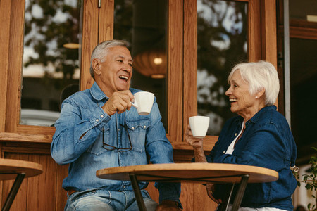 Smiling senior couple drinking coffee in cafe