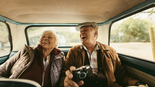 Senior couple enjoying traveling together by a car