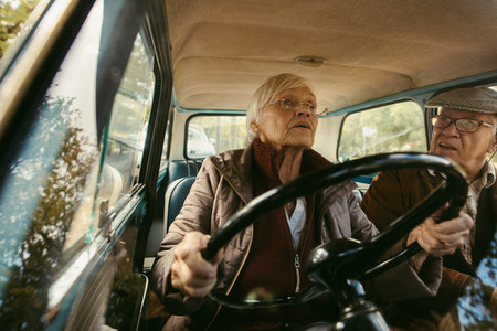 Elderly couple driving in vintage car