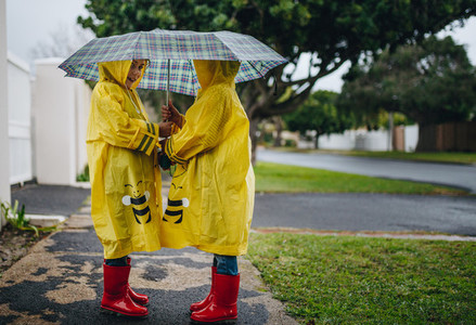 Little girls with raincoats and umbrella outdoors on a rainy day
