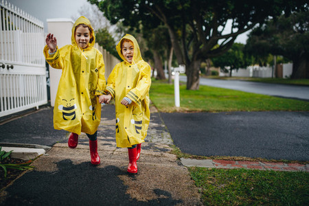 Twin sisters outdoors in raincoats