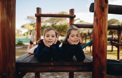 Twin sisters having fun at playground