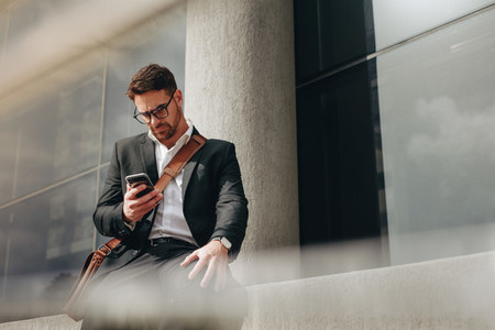 Entrepreneur sitting outdoors typing message on his cell phone