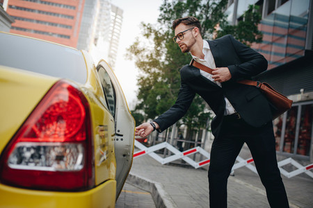 Businessman boarding a taxi to commute of office
