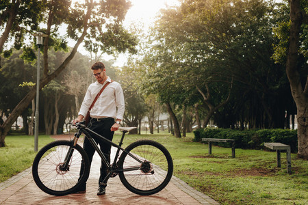 Smiling businessman standing in park with his bicycle