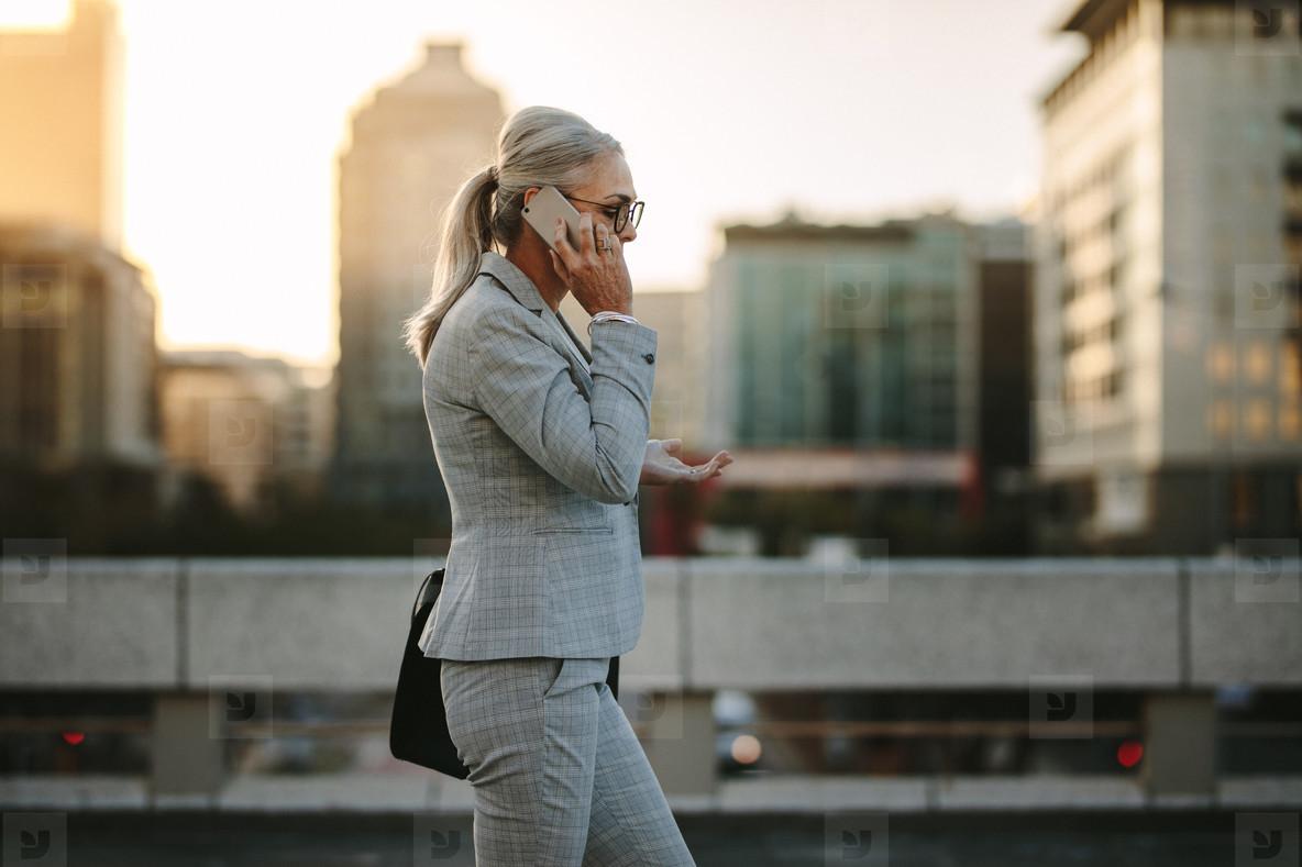 Senior businesswoman using cellphone on city street