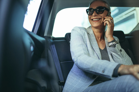 Business woman using phone inside the car