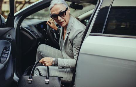 Sophisticated mature woman disembarking the car