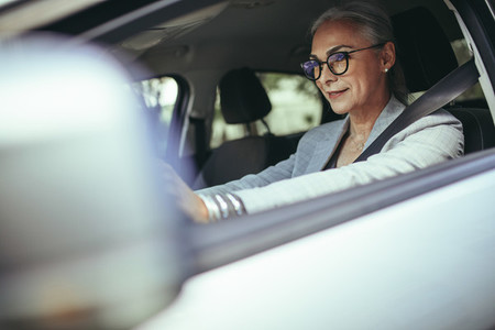 Senior female entrepreneur driving to office