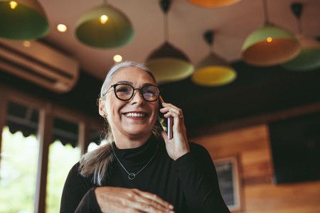 Woman talking on mobile phone at modern cafe