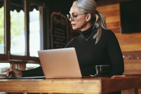 Senior businesswoman working at coffee shop