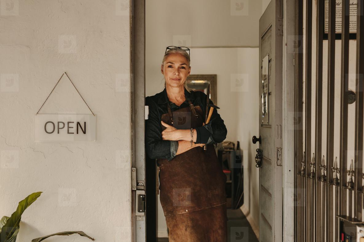 Female goldsmith standing at workshop door