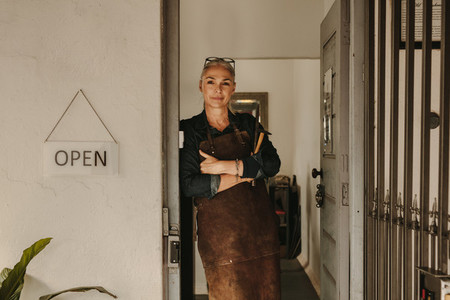 Female goldsmith standing at workshop door