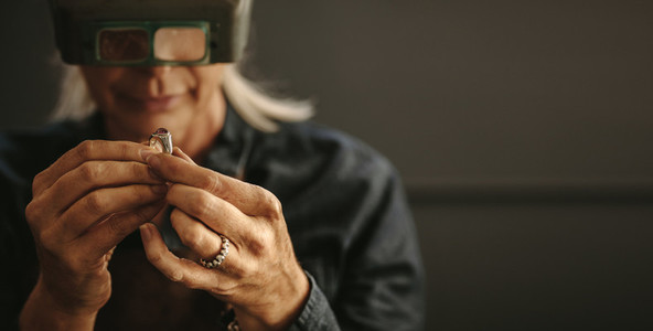 Jeweler inspecting diamond ring with magnifying glass