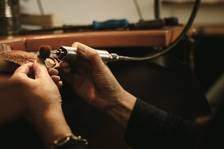 Jeweler polishing a gold ring at workbench