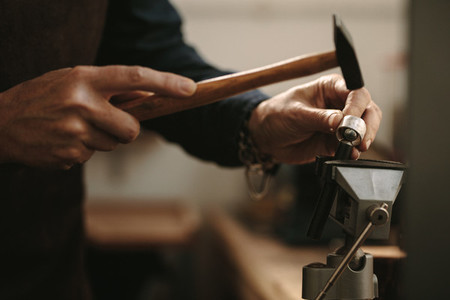 Jewelry designer shaping a ring at her workshop