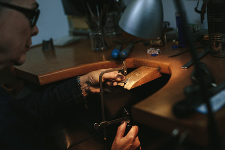 Female jewelry maker cutting metal with a band saw