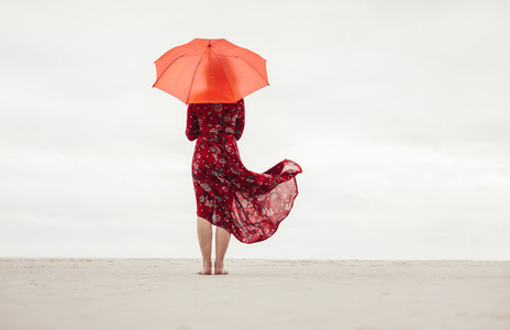 Woman under umbrella standing at the seaside