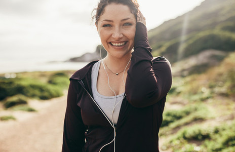 Cheerful female runner standing outdoors