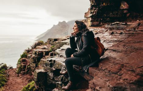 Female traveler relaxing on rocky mountain