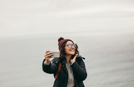 Smiling female traveler taking a selfie against ocean