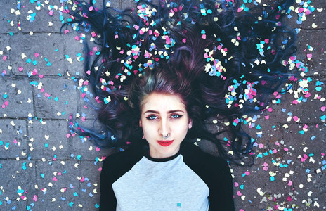 Cool young woman surrounded by confetti