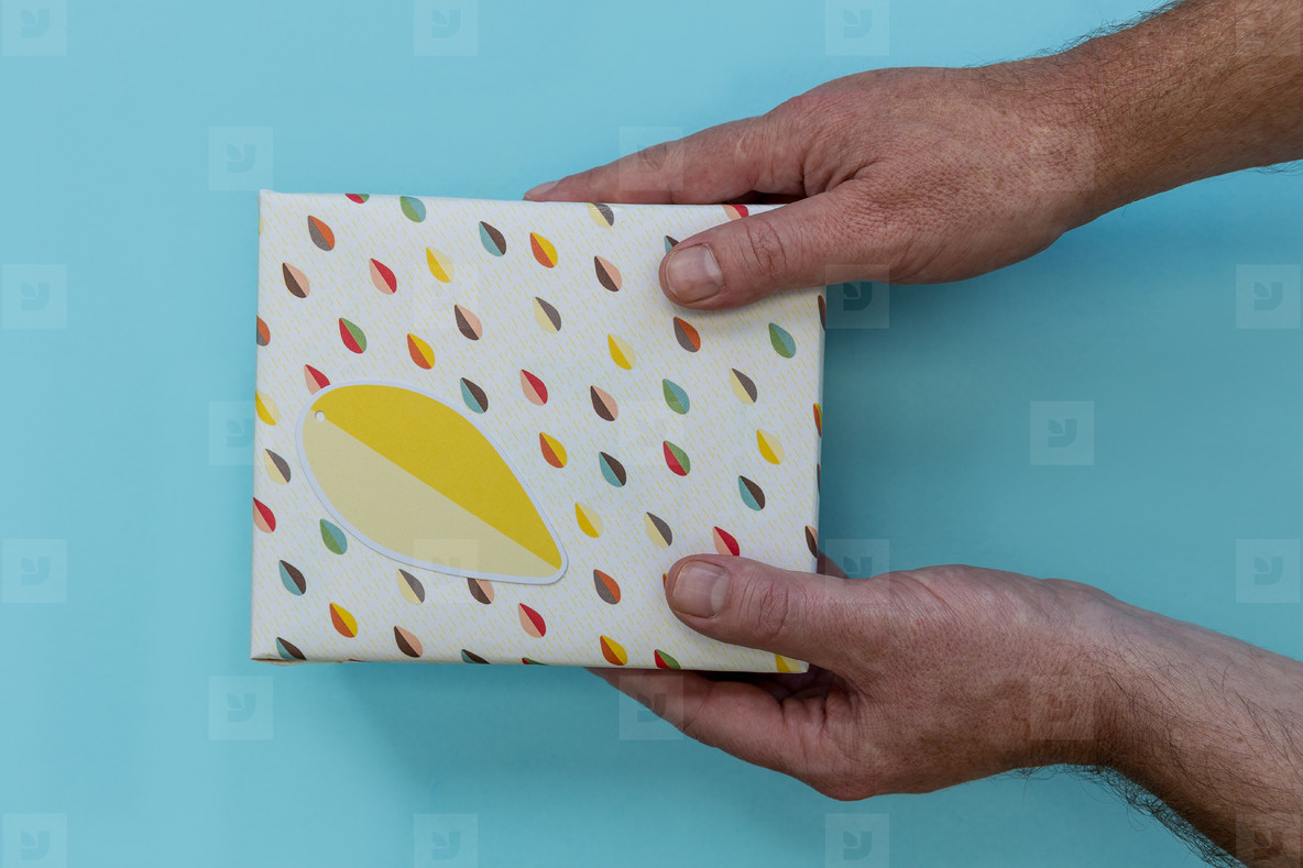 Hands giving birthday present gift box blue background
