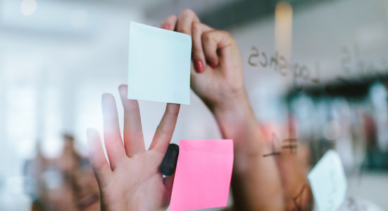 Creative professionals looking over a post it note