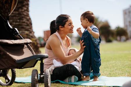Woman with her two kids sitting in park