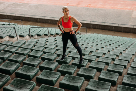 Woman athlete standing on the seats in the stands