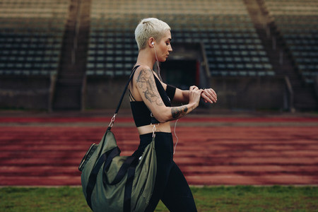 Woman runner walking inside an athletic ground