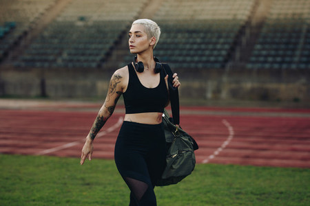 Woman athlete walking inside a track and field stadium
