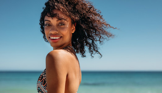 Side view of a woman with curly hair at the beach