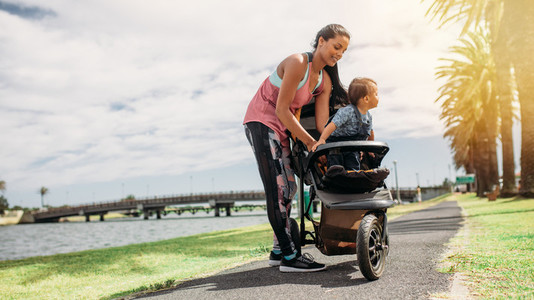 Mother placing her baby in a stroller