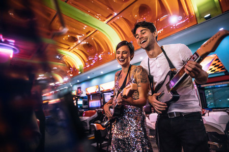 Smiling man and woman playing the guitar game at a gaming arcade
