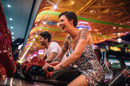 Happy couple having fun playing arcade racing games