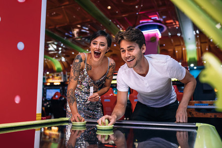 Happy couple playing coin operated air hockey game at a gaming p