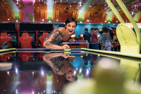Woman having fun playing air hockey game at a gaming parlour