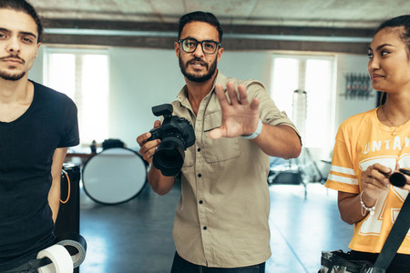 Photographer with his team during a photo shoot in a studio