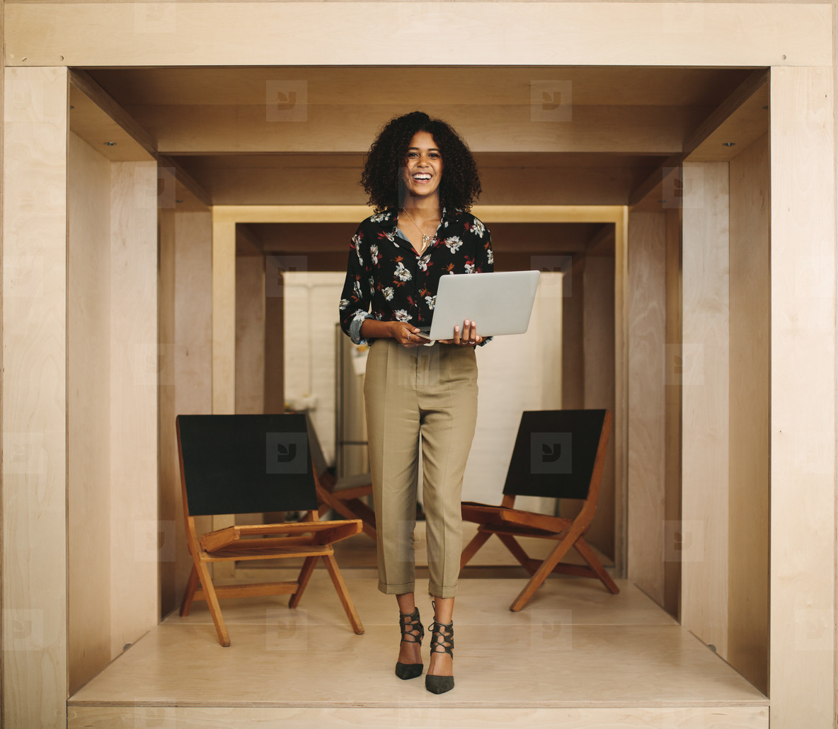 Portrait of a smiling woman entrepreneur standing in office hold